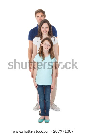 Full length portrait of family standing in line isolated over white background - stock photo