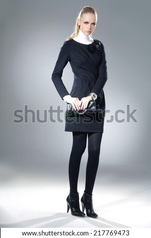 full-length Portrait of fashion model in autumn/winter clothes holding handbag posing - stock photo