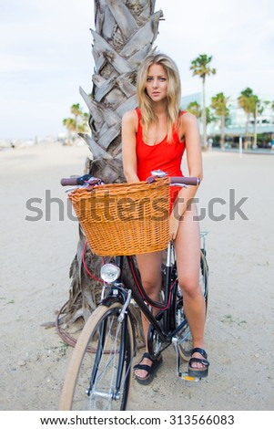 Full length portrait of  fashionable blonde hair woman dressed in trendy swimsuit standing with her retro bike on the beach, gorgeous female enjoying rest after riding on her classic bicycle along sea - stock photo