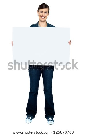 Full length portrait of fashionable trendy woman holding blank ad board - stock photo