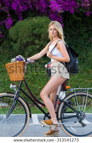 Full length portrait of fashionable young hipster girl riding in urban setting on her retro bike with a basket of beautiful flowers, glamorous woman enjoying recreation time while strolling on bicycle - stock photo