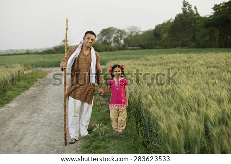 Full length portrait of father and daughter standing together in wheat field - stock photo