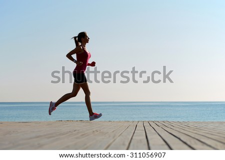 Full length portrait of female athlete doing an active fitness training on the wooden pier against beach, young sportswoman with good figure doing exercises for muscles of body during an active run - stock photo