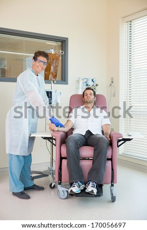 Full length portrait of female nurse examining patient receiving intravenous treatment in chemo room - stock photo