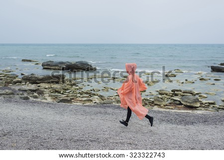 Full length portrait of female runner in movement. Running girl on the sea coast. Misty and rainy day is the best time for morning jogging. Sport and active lifestyle helps us to stay always fit - stock photo