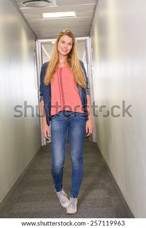 Full length portrait of female student standing at college corridor - stock photo