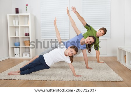 Full length portrait of fit family doing side plank yoga on rug at home - stock photo