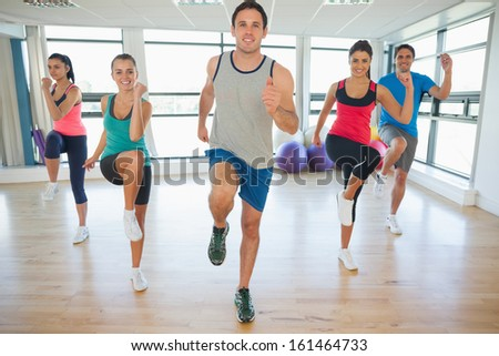 Full length portrait of fitness class and instructor doing pilates exercise in bright room - stock photo