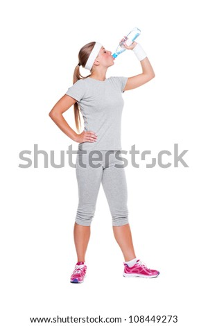 full length portrait of fitness woman drinking water. isolated on white background - stock photo