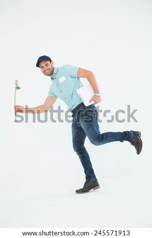 Full length portrait of flower delivery man running on white background - stock photo