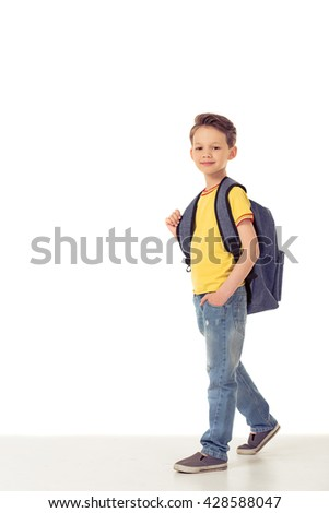 Full length portrait of funny little boy looking at camera and smiling while standing with school backpack, isolated on a white background - stock photo