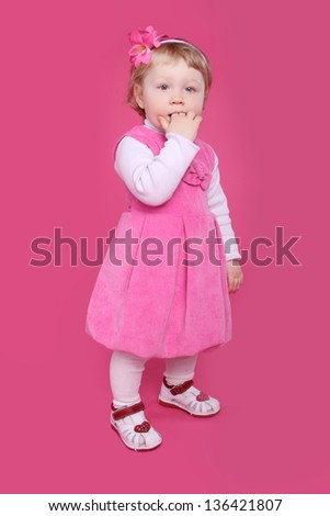 Full length portrait of funny little girl standing over pink background - stock photo