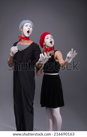 Full-length portrait of funny mime couple with white faces solemnly singing and waving their hands isolated on grey background with copy place - stock photo