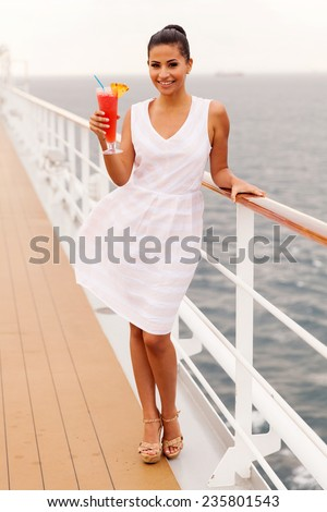 full length portrait of girl holding cocktail drink on a cruise ship deck - stock photo