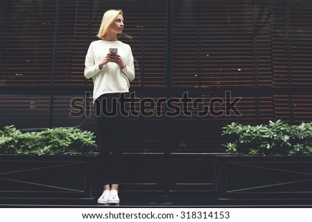 Full length portrait of gorgeous young woman holding smart phone in hand and looking to the empty copy space area for your text message or information,female hipster have chat conversation on phone - stock photo
