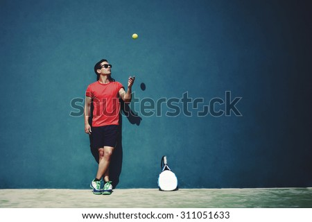 Full length portrait of handsome sportsman tossing a tennis ball while taking break after paddle game in sunny day outdoors, paddle player with copy space area for text message or advertising content - stock photo
