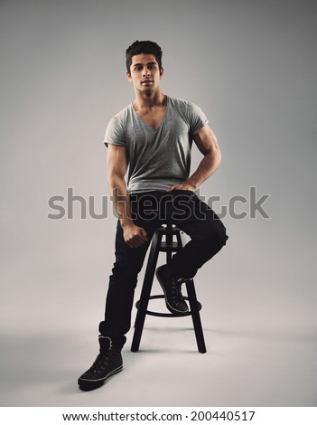 Full length portrait of handsome young man sitting on bar stool. Young hispanic male model over grey background. - stock photo