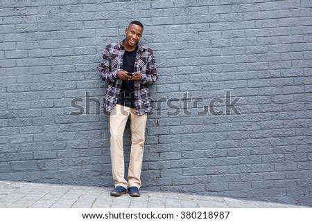 Full length portrait of handsome young man standing against a gray wall holding a mobile phone - stock photo