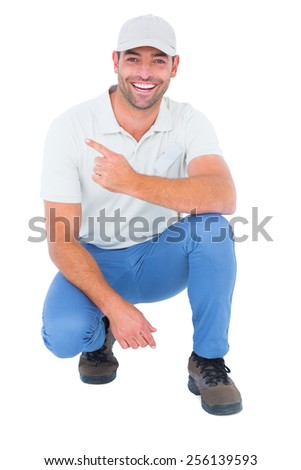 Full length portrait of handyman crouching while pointing on white background - stock photo