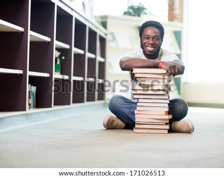 Full length portrait of happy African American student leaning on stacked books while sitting on floor at library - stock photo