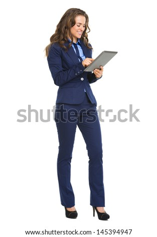 Full length portrait of happy business woman working with tablet pc - stock photo