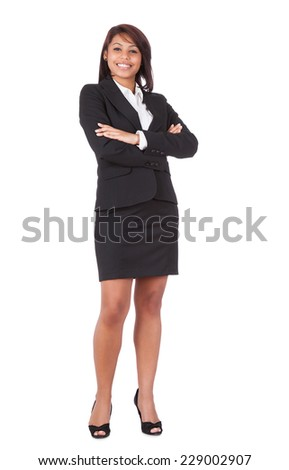 Full length portrait of happy businesswoman standing arms crossed over white background - stock photo