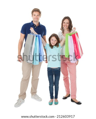 Full length portrait of happy family with shopping bags standing against white background - stock photo