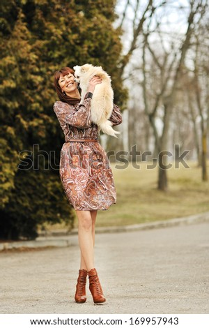 Full length portrait of happy female holding pet and looking good in a park - stock photo