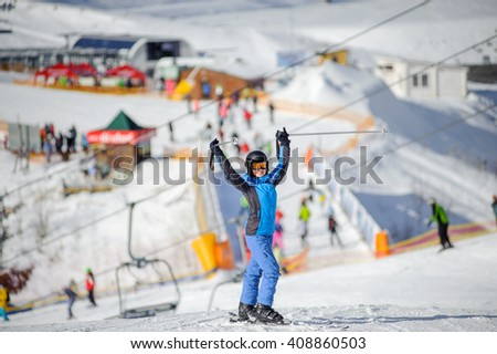 Full length portrait of happy female skier standing with arms up on a ski slope at a sunny day with lively ski resort on the background. Winter sports concept. Carpathian Mountains, Bukovel, Ukraine - stock photo