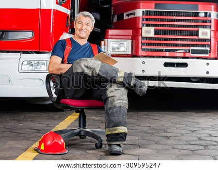 Full length portrait of happy firefighter sitting on chair against trucks at fire station - stock photo