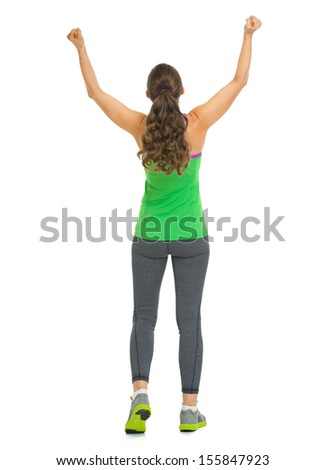 Full length portrait of happy fitness young woman rejoicing success . rear view - stock photo
