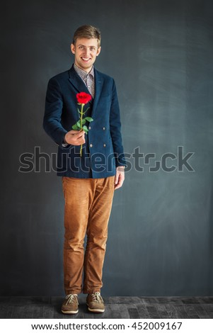 Full length portrait of happy handsome man with red rose standing against grey wall background - stock photo