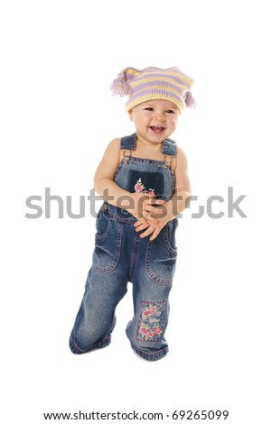 Full length portrait of happy laughing cute baby girl making her first step on white background - stock photo