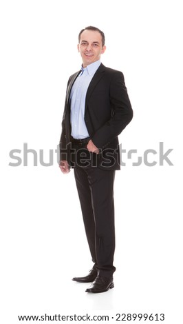 Full length portrait of happy mature businessman standing against white background - stock photo