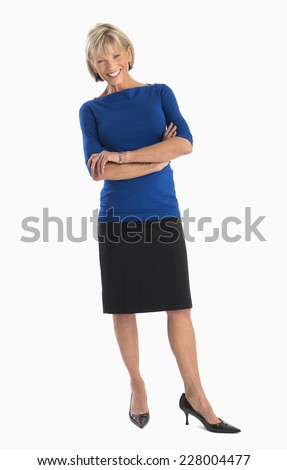 Full length portrait of happy mature businesswoman standing arms crossed over white background - stock photo