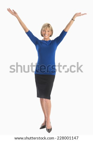 Full length portrait of happy mature businesswoman with arms raised over white background - stock photo