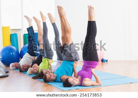 Full length portrait of happy men and women doing Pilates exercises in gym - stock photo