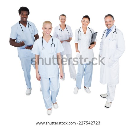 Full length portrait of happy multiethnic medical team standing over white background - stock photo