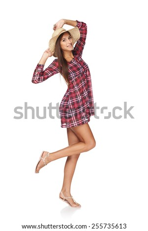Full length portrait of happy playful woman in country style pointing at herself, isolated on white  background.  Smiling woman wearing checkered summer dress and broad-brim straw hat. - stock photo