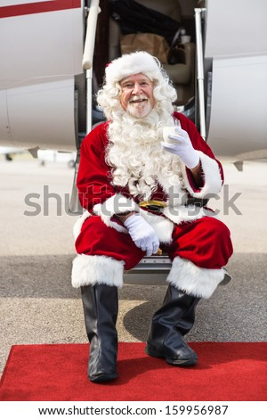 Full length portrait of happy Santa Claus holding milk glass while sitting on private jet's ladder - stock photo
