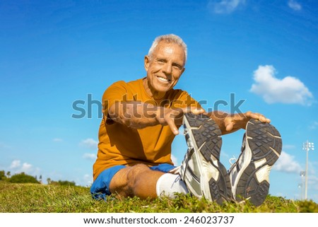 Full length portrait of happy senior man in sportswear stretching on field - stock photo