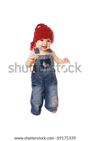 Full length portrait of happy smiling pretty baby girl making her first step on white background - stock photo