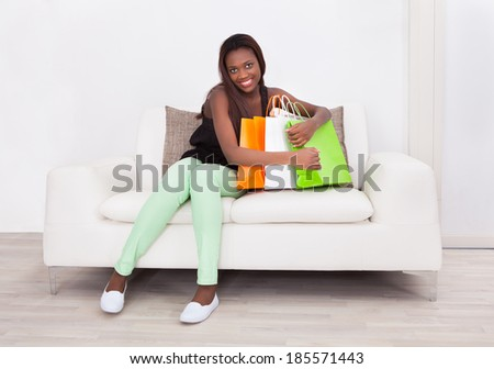 Full length portrait of happy woman embracing shopping bags on sofa in living room - stock photo