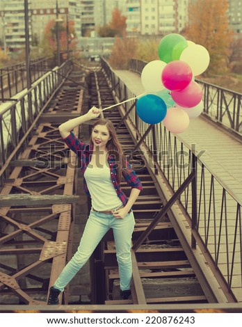 Full length Portrait of Happy woman with colorful balloons standing on old retro vintage metal bridge in perspective Young adult girl wearing casual dress Looking at camera against houses  - stock photo