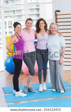 Full length portrait of happy women standing arms around in gym - stock photo