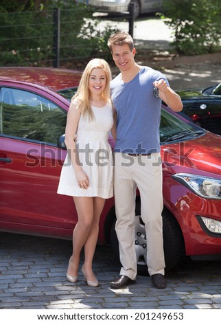 Full length portrait of happy young couple holding key by new car - stock photo
