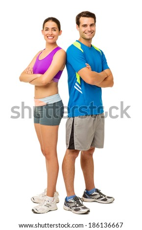 Full length portrait of happy young couple in sports wear standing back to back over white background. Vertical shot. - stock photo