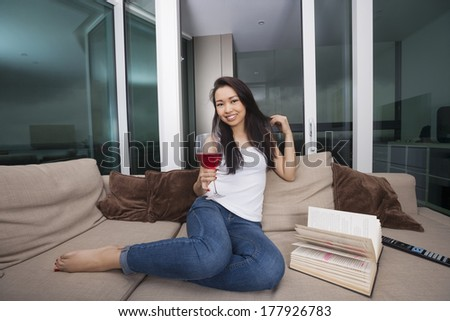 Full length portrait of happy young woman having red wine in living room - stock photo