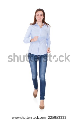 Full length portrait of happy young woman in smart casuals running against white background - stock photo