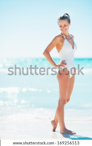 Full length portrait of happy young woman on beach - stock photo